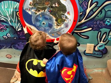 two children in batman and superman costumes staring at spinning wheel amazed