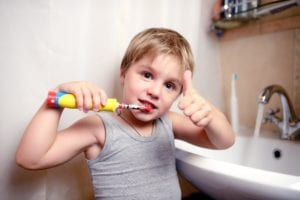 boy brushing his teeth and giving a thumbs up