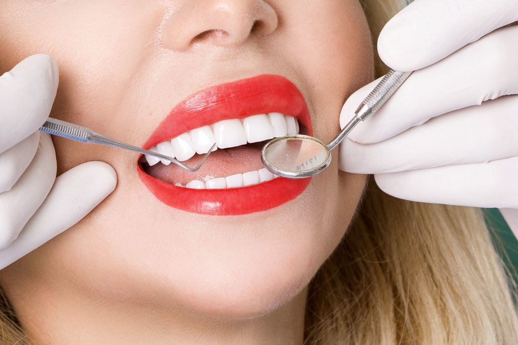 Closeup of a woman with lipstick getting a dental exam