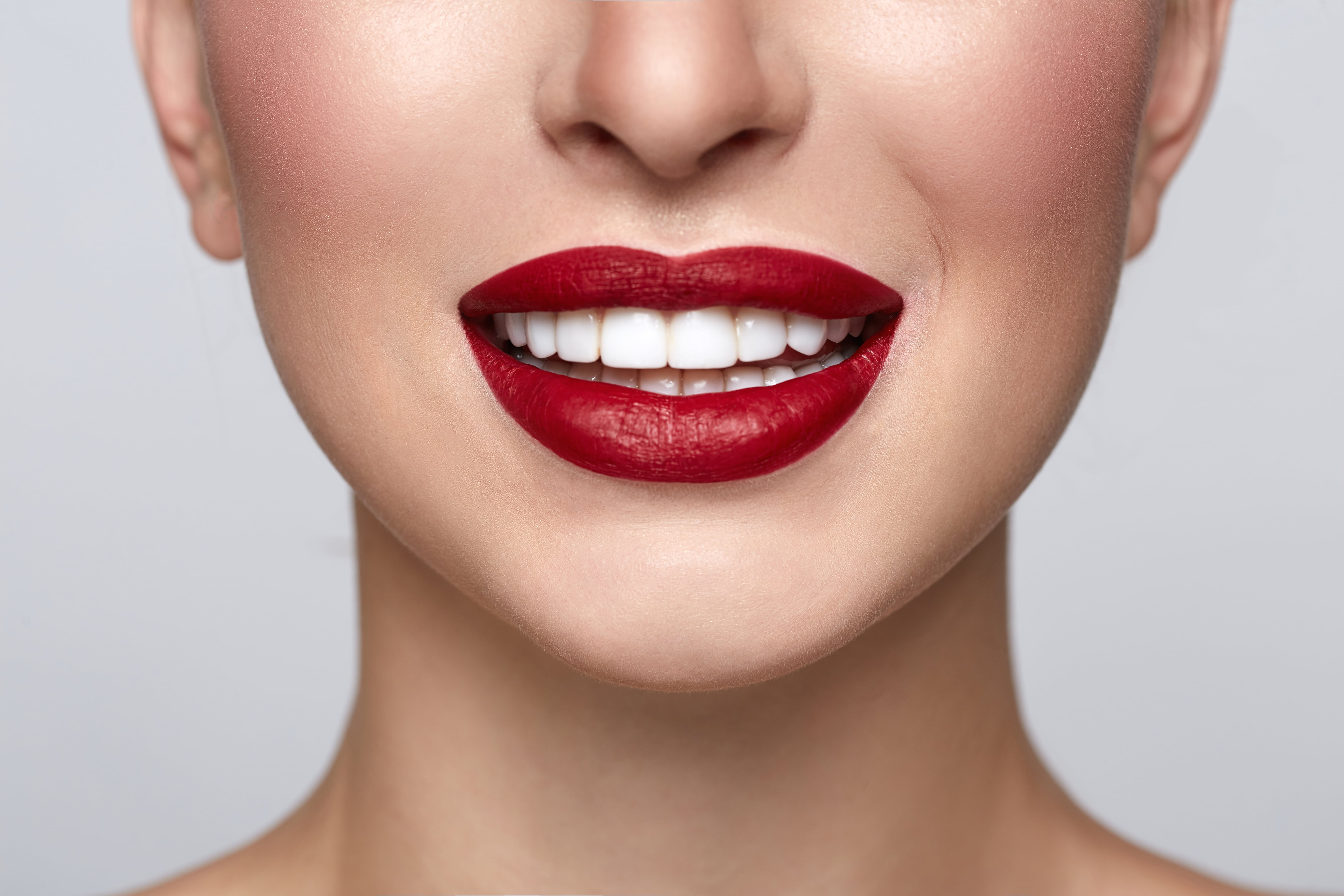 Lower half of a woman's smiling face with white teeth and red lipstick