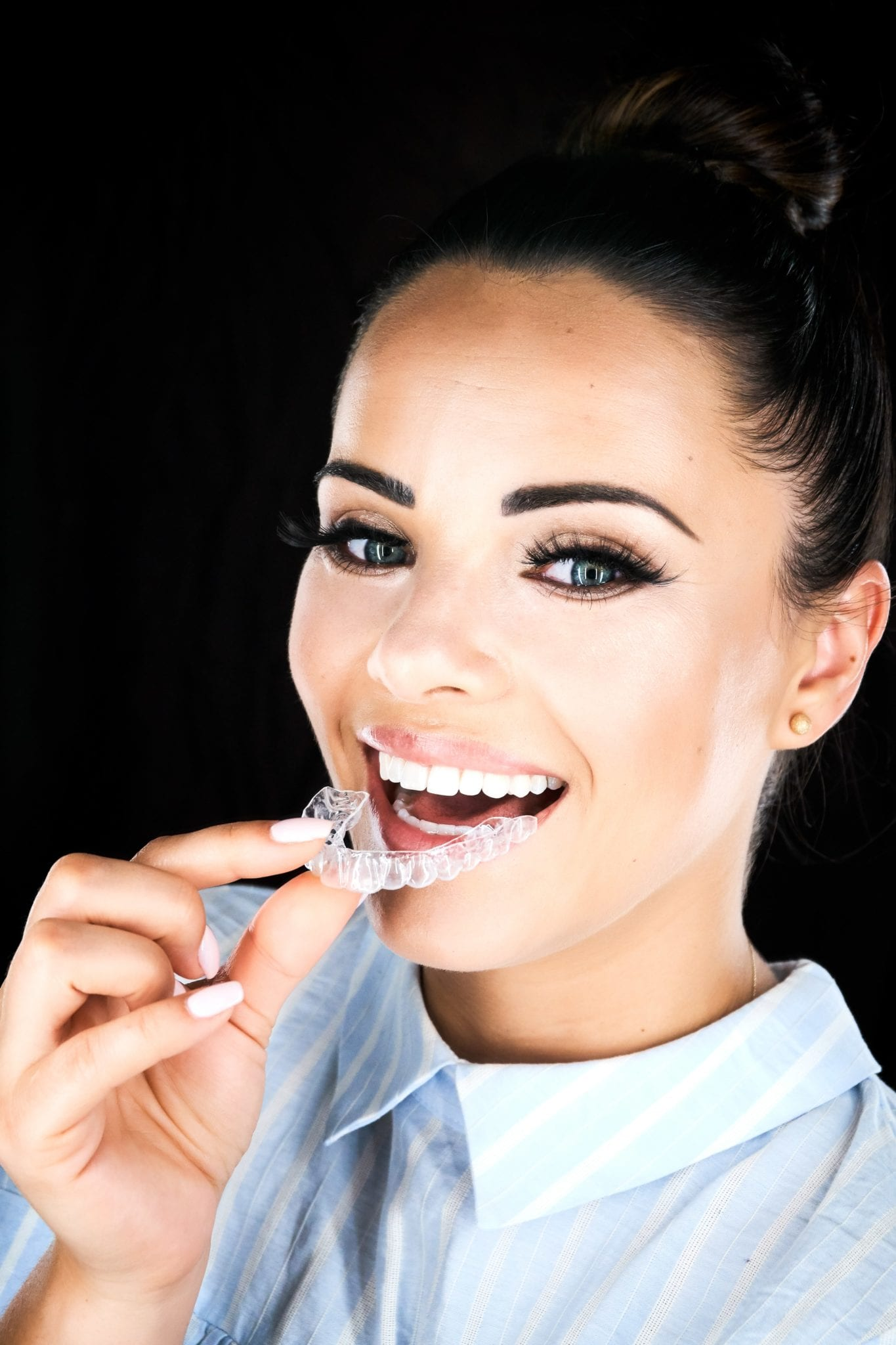 Woman putting in a clear aligner