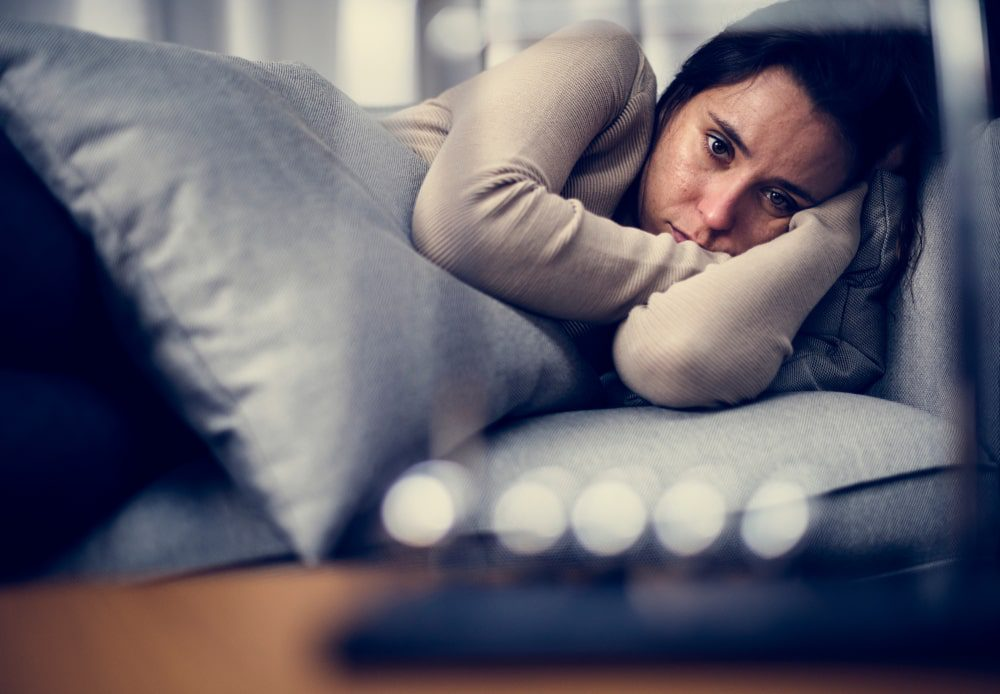 Woman lying on couch, snuggling a pillow and looking unhappy