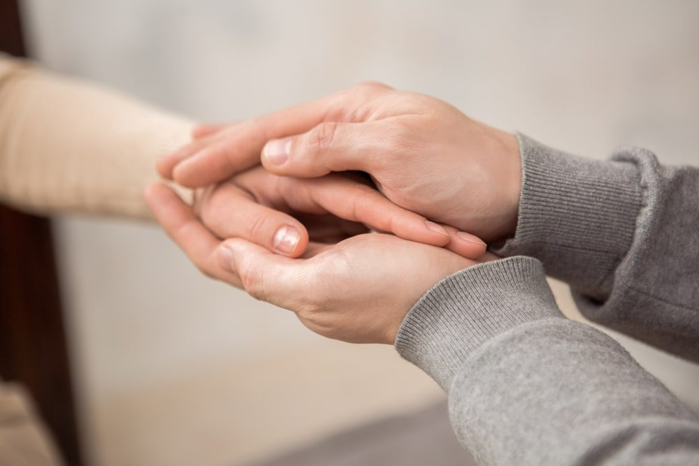 A female hand being held in between to male hands offering support