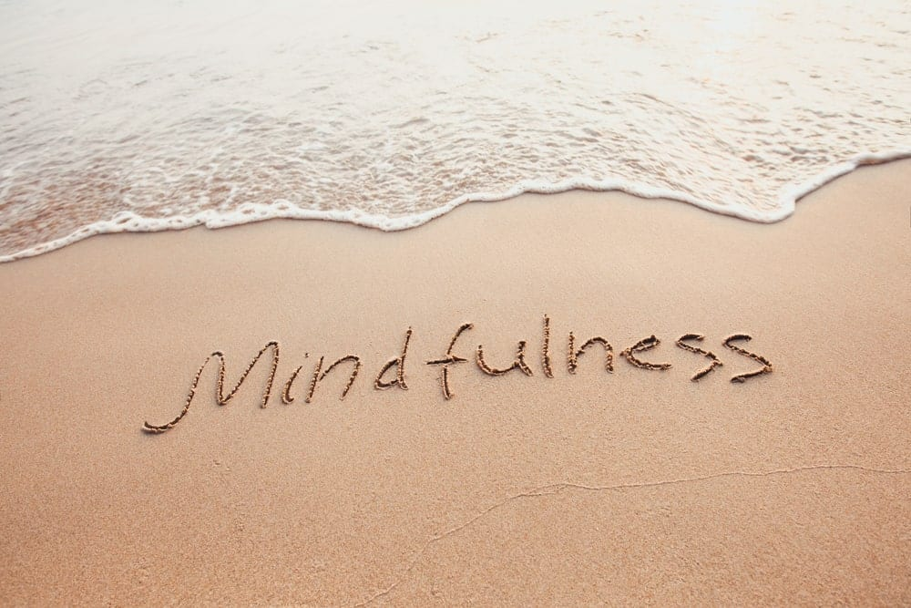 "The word ""mindfulness"" written in the sand at the beach"
