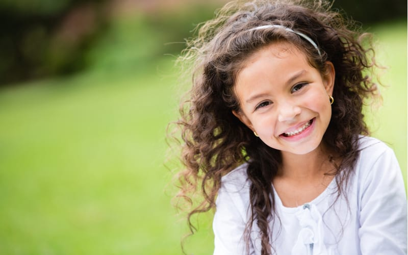 little girl with curly hair smiling as wind blows