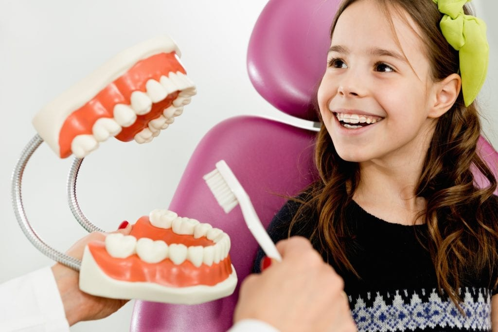Girl learning how to brush her teeth with a giant mouth model and toothbrush