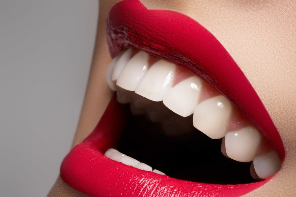 Woman smiling in red lipstick with white teeth