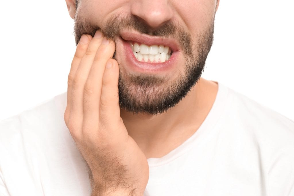 Man grimacing and holding his cheek