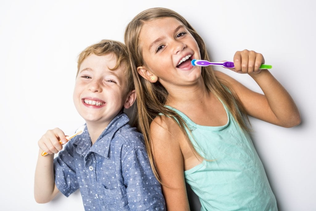 Brother and sister brushing teeth