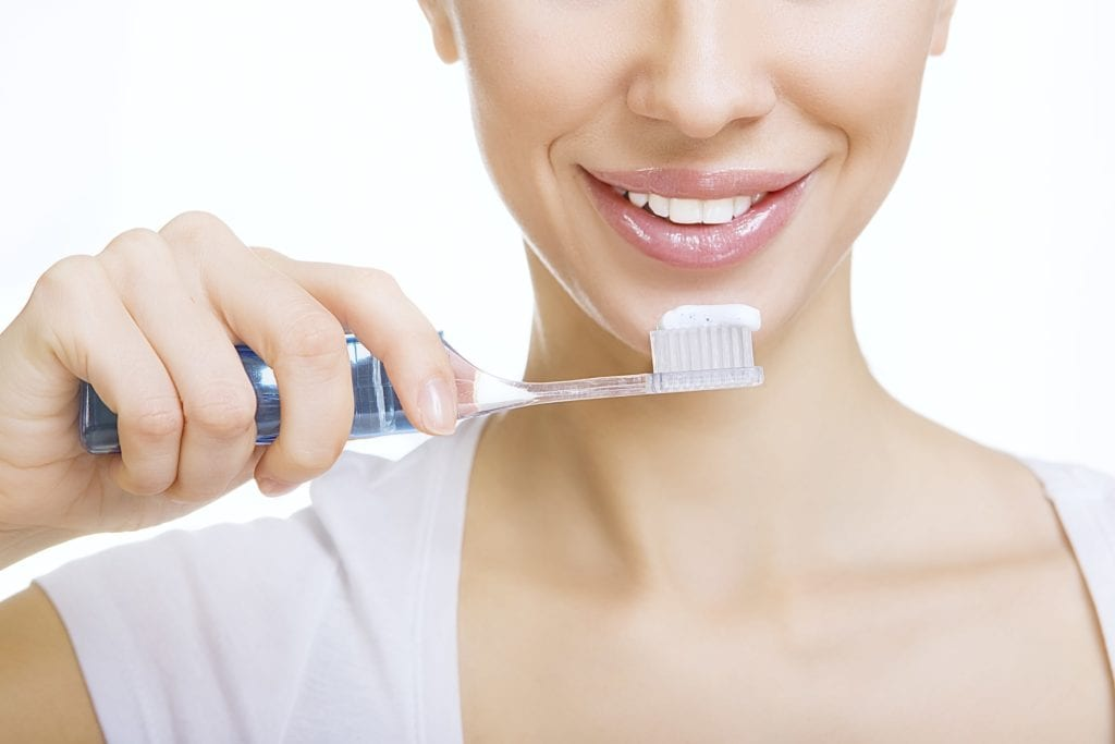 Woman holding a toothbrush with white toothpaste