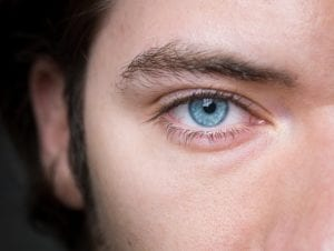 closeup of person with blue eyes half face