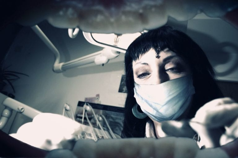 inside of the mouth view of dentist cleaning teeth