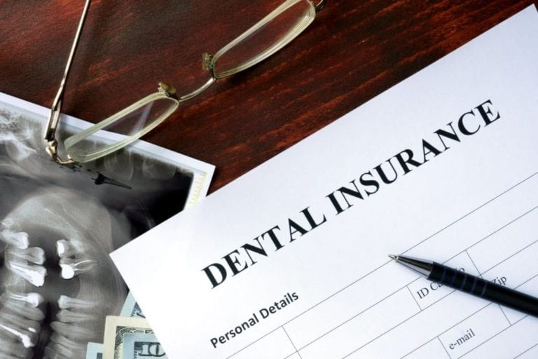 Photo of dental insurance paper with a pen on top, glasses above and an x-ray under Dollar bills