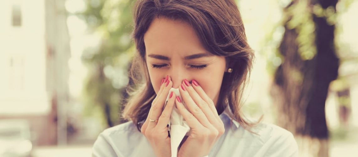 Woman blowing her nose due to allergies