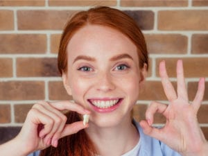 A patient holding an extracted tooth and smiling while flashing OK sign