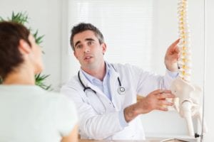 doctor talking to patient showing spine model