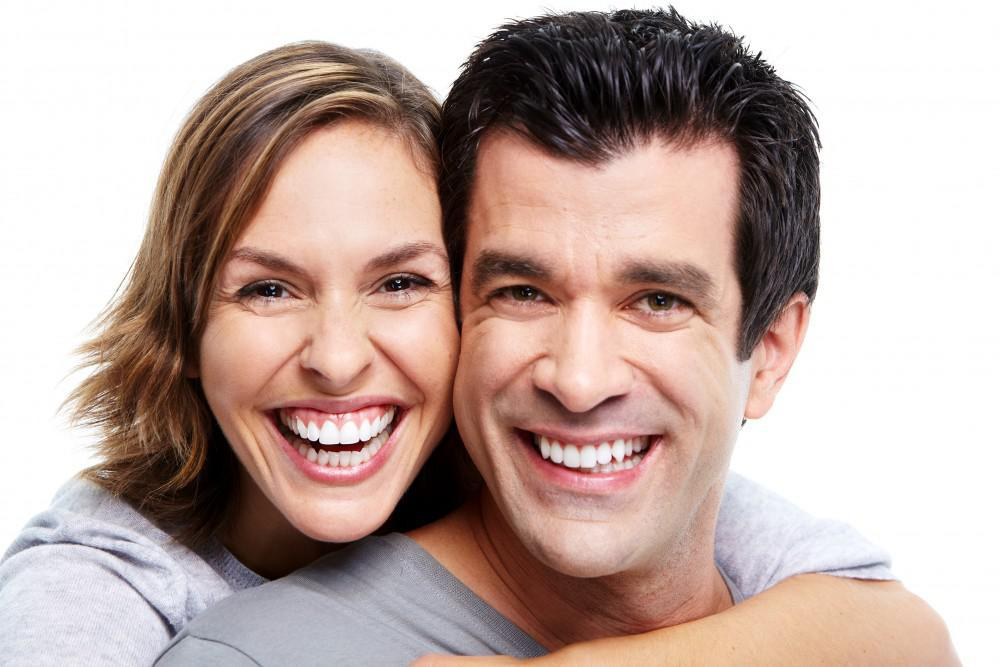 man and woman grinning wide white background
