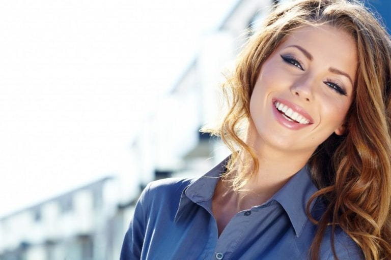 attractive young woman smiling blue shirt