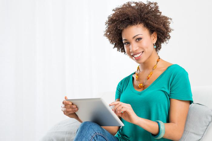 african american woman smiling holding ipad