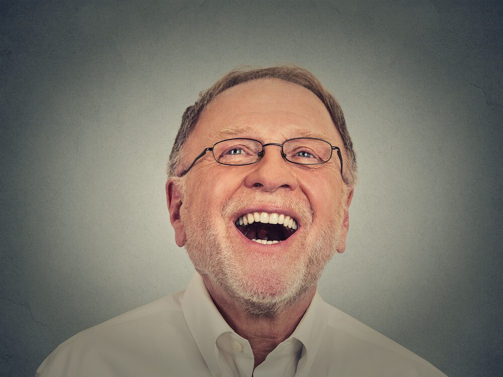 elderly man smiling teeth grey background